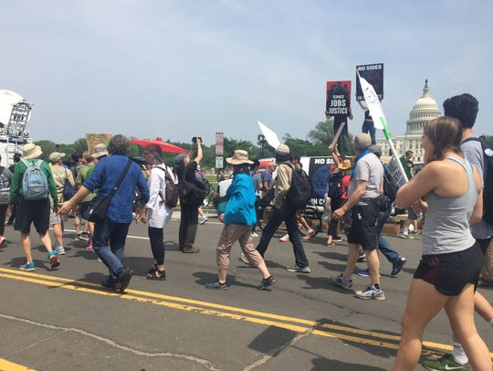 People's Climate Marchers walk past the U.S. Capitol.