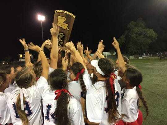 North DeSoto Lady Griffins  holds up their championship trophy.