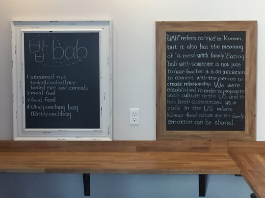 """Signs at the new Bab Café explain the meaning of the Korean term """"bab."""" The restaurant also has locations in Seoul."""