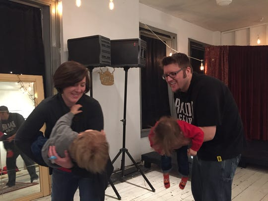 Jodie and Andy Bishop hold their one-year-old twin sons, Remy and Dean Bishop, while dancing to music in Molly Murphy's Queen City Music Studios music class for toddlers on Monday, March 6, 2017.