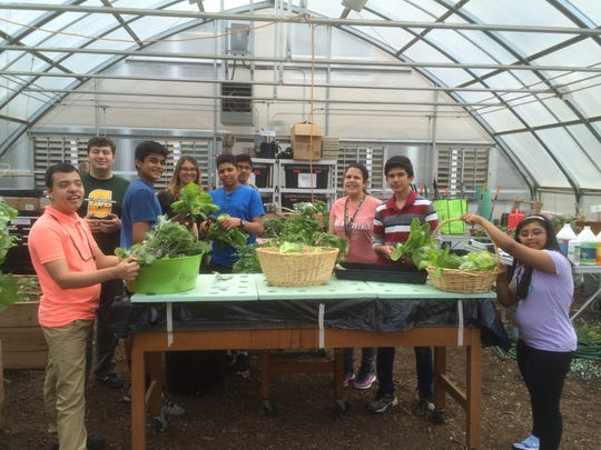 Teacher Marissa Freeman and her students in their greenhouse at J.P. Stevens High School in Edison.