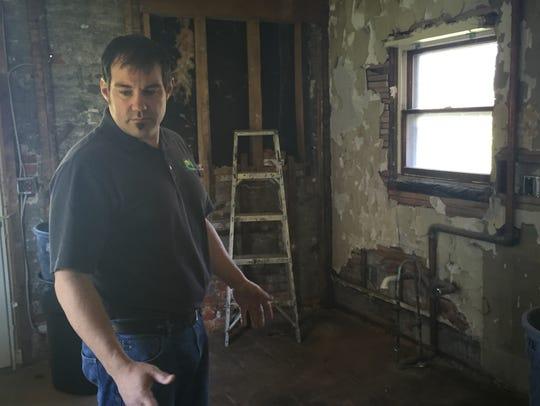 Dennis Delor looks around a kitchen being restored