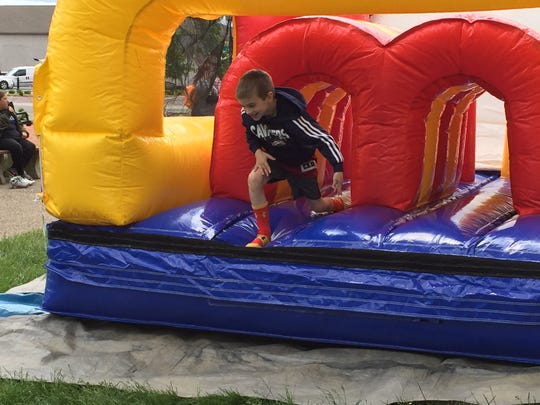 A child plays in a blow up obstacle course Saturday