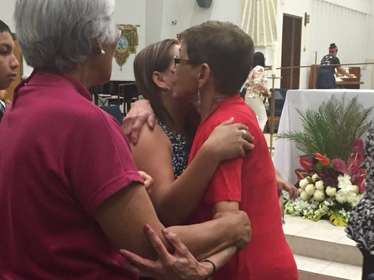 Doris Concepcion, right, is greeted by church goers,