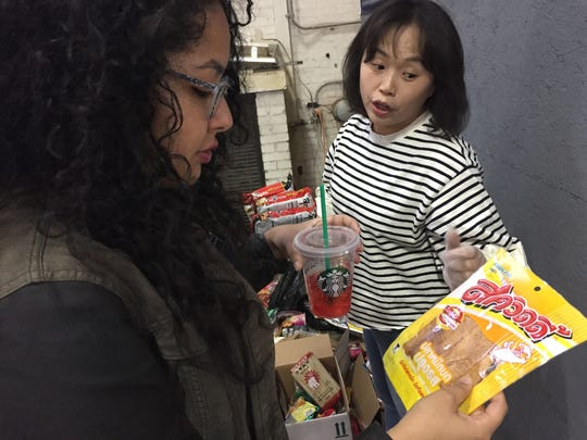 Sun Kim, right, explains to Vanessa Pacheco why dried squid is a popular snack among some Purdue students. Pacheco and Kim, both with the Office of Civic Engagement and Leadership Development at Purdue, were working Monday during Project Move Out, sorting what students left behind in dorms at the end of the semester.