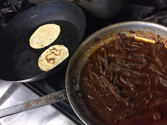 Large strips of skirt steak stew in a skillet with