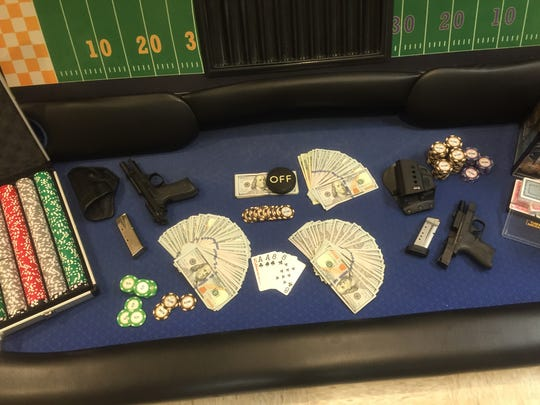 Cash and guns were collected after Smyrna Police executed a search warrant at two locations pertaining to charges of illegal gambling.