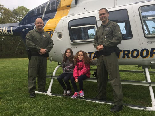 Second-grader Avery Torres, 8, (left) and first-grader Abrianna Goff, 7, pose for pictures with New Jersey State Police Troopers Bill Munyon (left) and Evan Curtiss. The troopers pilot one of three NJSP Bell 206 helicopters. The helicopter was sent on Thursday to take part at the Millville school system's annual Student Learning and Technology Showcase, held at Holly Heights  Elementary School.