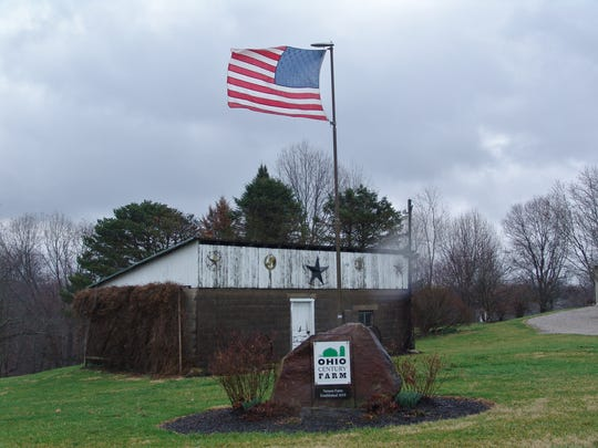 An American flag flies by a building on the Vernon Farm where the ODA Ohio Century Farm recognition sign stands.