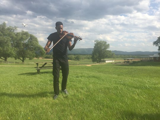 "Violinist Eric Stanley, of Richmond, performs in a meadow in Waynesboro on Sunday, May 14, 2017, while a drone flies around him to record a music video. The video is for the song, ""Pull Thru,"" written Matt Johnson for his mother who is facing her third battle with cancer. Stanley drove straight from a Mother's Day church service in Richmond to Waynesboro for the filming."