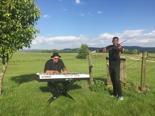 "Matt Johnson, of Fishersville, and Eric Stanley, of Richmond, perform Johnson's song, ""Pull Thru,"" for a music video on a meadow in Waynesboro on Sunday, May 14, 2017. The song was written by Johnson for his mother, who she faces her third battle with cancer. In 2013, Alex Johnson was first diagnosed with breast cancer."