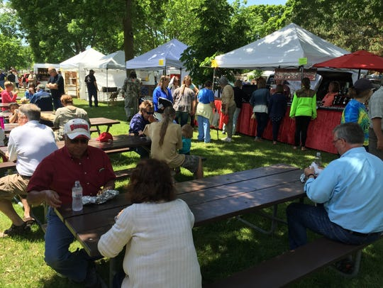 Visitors explore the booths and eat food at the Fond