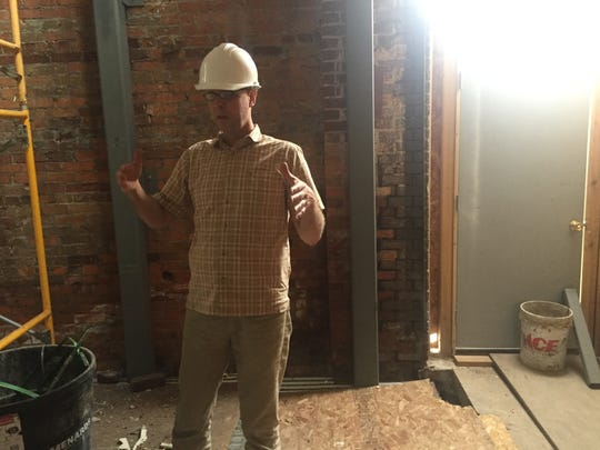 Kevin Korpela, one of the co-owners of Downtown Grocery, stands in front of the brick walls of the building, which have been reinforced with steel to keep the building upright.