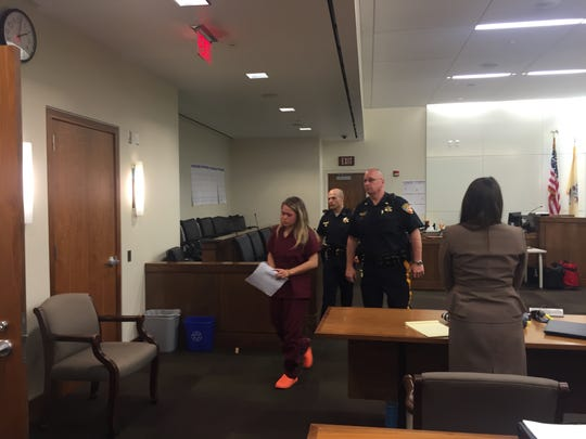 Raquel Garajau, 20, of Tinton Falls, is led out a courtroom in Monmouth County Superior Court after she made her first appearance May 16. Garajau was charged with numerous offenses, including murder and robbery, in an indictment with her boyfriend, 21-year-old Joseph Villani, of Ocean Township.