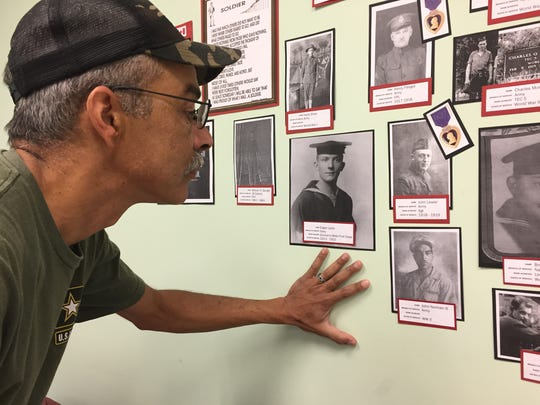 John Norman looks at the Military Honor Wall at Grove Family Library where photos of three generations of John Normans is displayed, including his grandfather, John Normal III and father John Norman IV.
