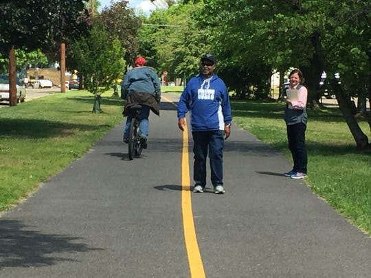 Bikers, walkers and joggers share the popular mile-long Merchantville trail that runs along Chestnut Avenue on the edge of  the redevelopment area where new housing and retail development is being proposed.  Photo by Carol Comegno/Staff Photographer