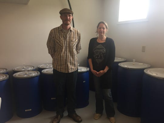 Gerrid and Sadie Frankes stand in front of barrels