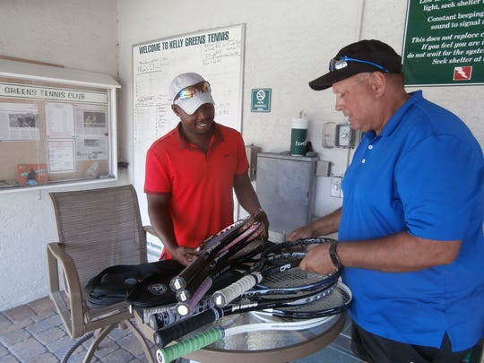 Palmira director Paul Segodo, left, looks over some rackets donated to his Tennis for a Better Life Foundation by members of Kelly Greens Golf & Country Club with director John Ramsey II.