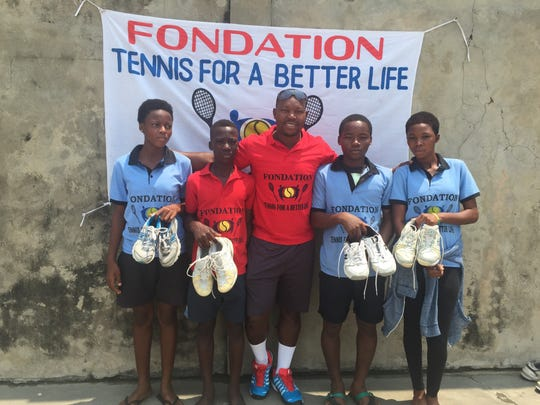 Paul Segodo, director of tennis at the Palmira, gathers with youngsters in Benin, Africa, who received tennis shoes donated by area players during a visit last summer on behalf of his Tennis for a Better Life Foundation.