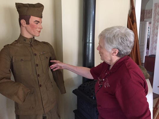 Shirley Schmidt, secretary of the Sanilac County Historical Society, looks at a uniform issued to Frank Erbe.