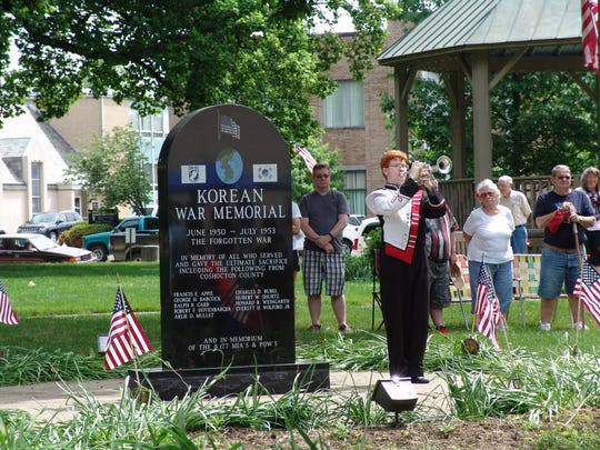 Jacob Heading, member of the Coshocton High School band, plays taps by the Coshocton County Korean War Memorial during the 2016 Memorial Day ceremony at the court square.