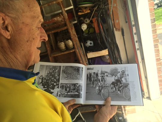 Augie Mueller, of Vestal, looks at a photo from the Broome County Historical Society of his then 12-year-old daughter riding a tandem bike with him on a 600-mile ride to Maine.