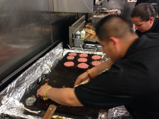 A worker lays down meatless patties on the griddle