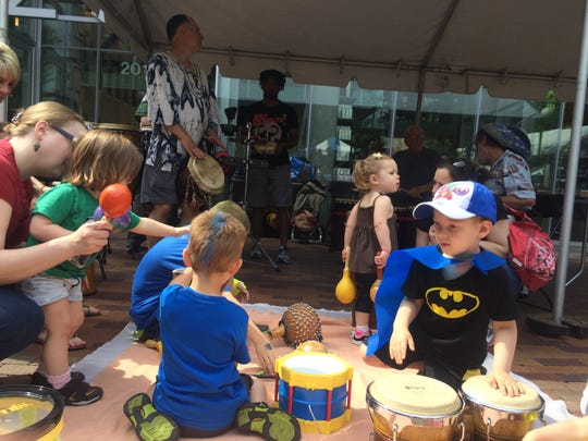 The caped Liam Gilroy, 4, drums along to the Yahoo Drummers with some bongos at the Iowa Arts Festival on Saturday.