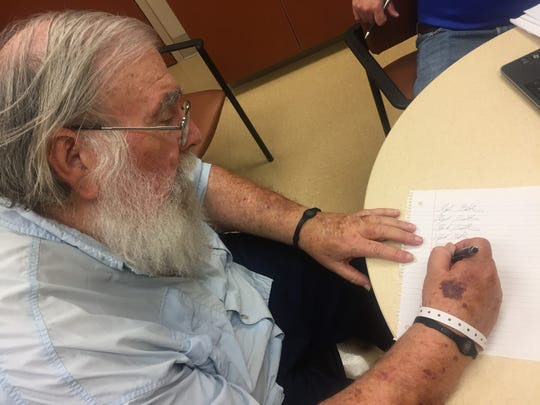 Clyde Butcher practices writing his signature after a stroke affected his ability to use his right arm.