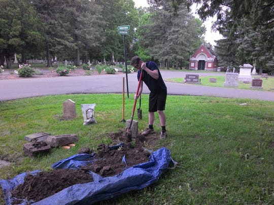 University of Iowa student Jace Bloomer works at Aspen Grown Cemetery in Burlington. Bloomer and his father, Mike, operating StoneDoctorz, a gravestone restoration service.