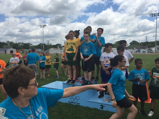 Fifth-graders line up for awards after a relay race