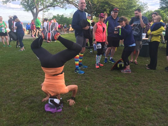 Some pre-race ... stretching?, in Battery Park in Burlington near the start line for the Vermont City Marathon on Sunday, May 28, 2017. Aleida Castillo of Leominster, Massachusetts, balances on her head and poses for Nannette Taylor of Shirley, Massachusetts, who snapped a picture.