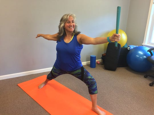 Simchah Huizar demonstrates warrior 2 yoga pose with a club bell at her studio in Selmer on May 26, 2017.