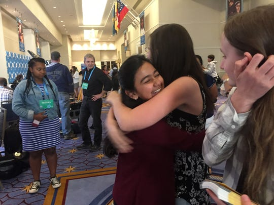 Naysa Modi, of Monroe, Louisiana, gets a congratulatory hug. She's among the final 15 competitors in the Scripps National Spelling Bee.