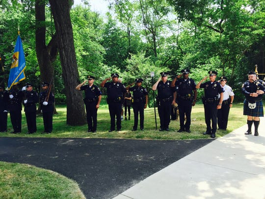 Wilmington Police officers pay salute a memorial to