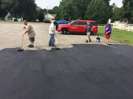 Eric Greene, his parents and a friend work on resurfacing
