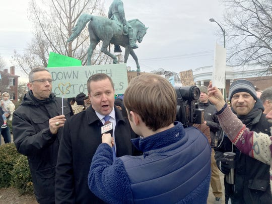 """Protesters shout as Virginia gubernatorial candidate Corey Stewart gives interviews to local television stations in February about his opposition to removing a Robert Lee statue from a Charlottesville, Virginia, park. """"I believe in protecting historical monuments,"""" Stewart says. """"The KKK is a racist organization that has no place in Virginia."""""""