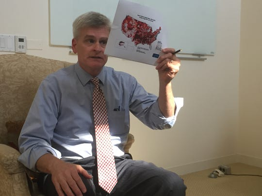Sen. Bill Cassidy, R-La., explains his health care bill to reporters in his office last month.
