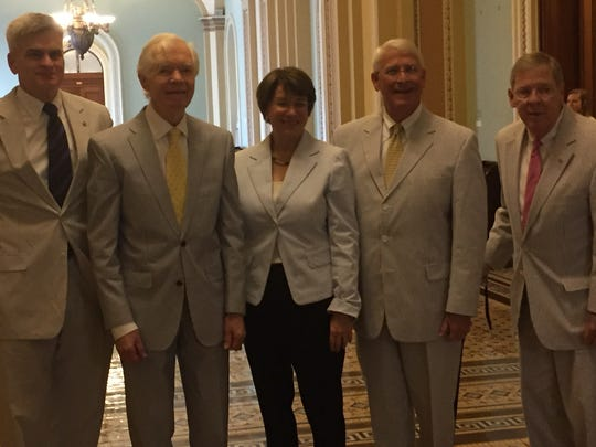 Sens. Bill Cassidy, R-La., (left), Thad Cochran, R-Miss., Amy Klobuchar, D-Minn. Roger Wicker, R-Miss., Johnny Isakson, R-Ga., take a picture Thursday outside the Senate chamber for National Seersucker Day.