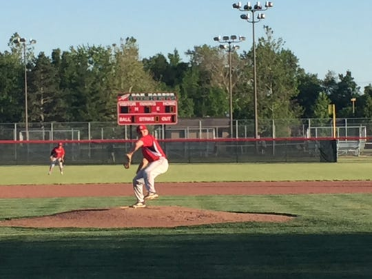 Post 114's Madison Jaso throws a pitch Thursday with Gibsonburg teammate Ryan Clark behind him.