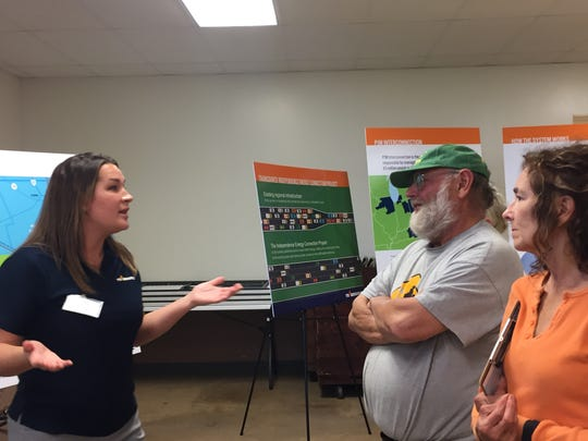 Abby Foster, a Transource Energy community affairs representative, explains the project to local residents Walter Blumenfeld and Linda Dickinson.