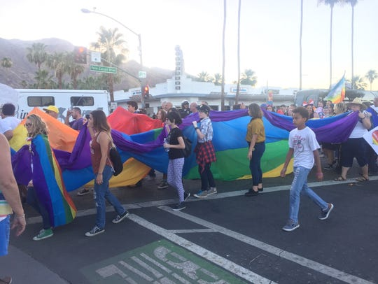 Marchers carry a large rainbow flag at a unity march