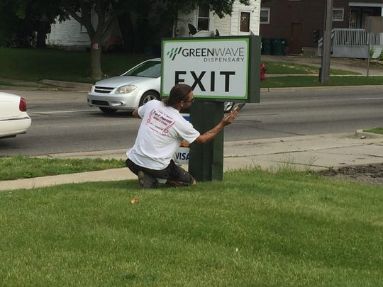 An employee at the Greenwave medical marijuana dispensary in Lansing put a fresh coat of paint a couple months ago on one of its signs. City Council passed Thursday night an ordinance to license and regulate marijuana establishments.