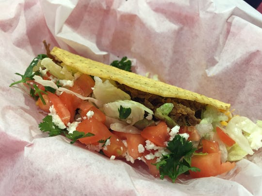A beef taco from Fuzzy's Taco Shop is served on a crispy (or soft) tortilla and topped with garlic sauce, lettuce, tomatoes, shredded cheese, cilantro and feta cheese.