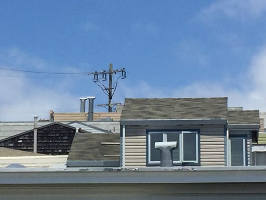 An electric pole rising above rooftops in San Francisco.
