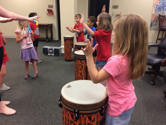 Kids practice with drums and rhythm sticks for the