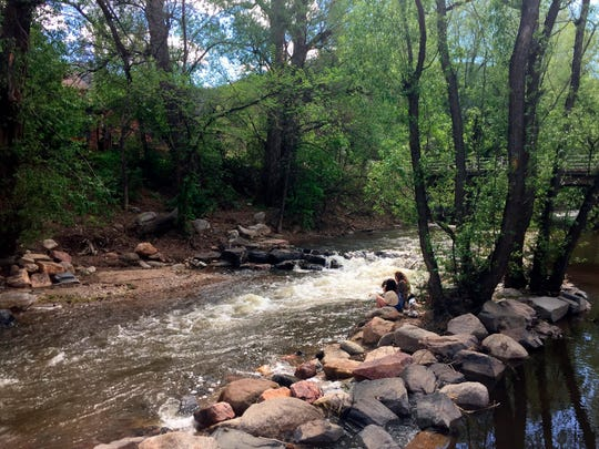 This May 13, 2017 photo shows people relaxing along Boulder Creek in Boulder, Colo. The 8-mile Boulder Creek Path alongside the waterway is a scenic trail where you can stroll, bike or just sit for a few peaceful moments. (AP Photo/Beth J. Harpaz)