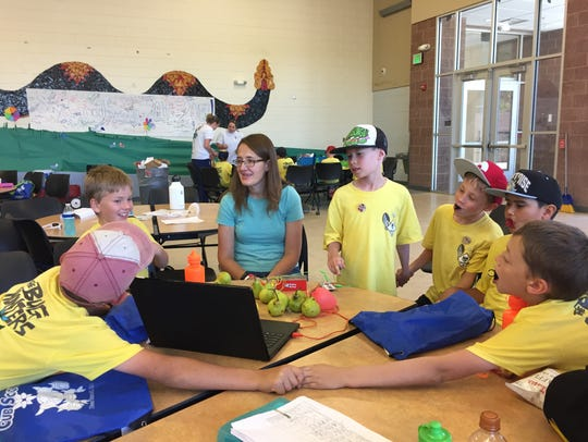 Kim Bezzant, a Cub Scout volunteer, shows kids how