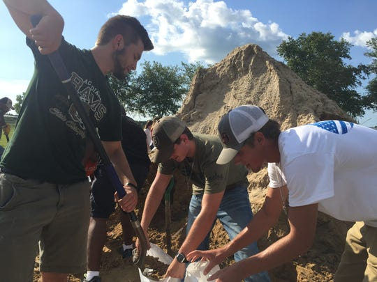 People are seen bagging sand at one of the Lafayette Consolidated Government sand bagging stations located at 400 N. Dugas Road off University Avenue. Pictured from left are Jaxon Kampf of Scott, Nick Cummings of Lafayette and Kaleb Mitchell of Scott. The second station is located at 1017 Fortune Road, Youngsville. People need to bring their own shovel and manpower. Sand and bags are free to Lafayette Parish residents.