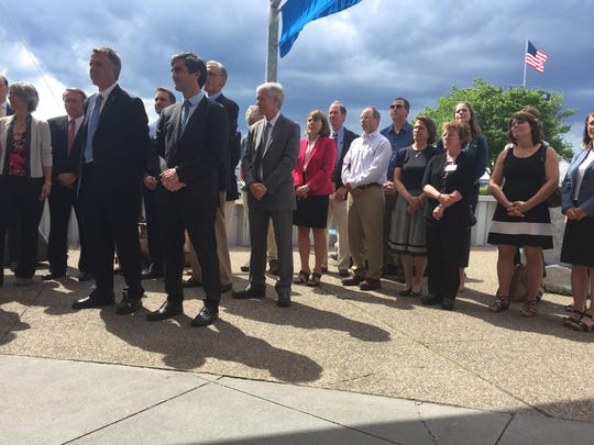 Gov. Phil Scott and Mayor Miro Weinberger stand with business leaders, environmentalists, mayors and other supporters of the Vermont Climate Pledge Coalition on June 20, 2017